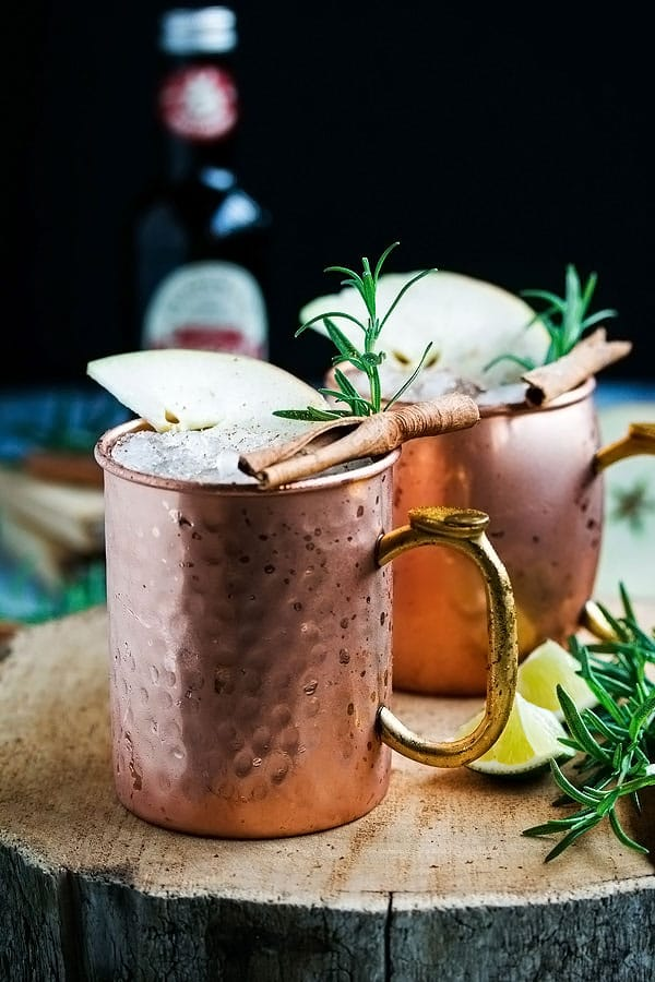 two copper mugs with apple cider moscow mule inside.  the mugs are topped with a piece of cinnamon, a slice of apple and a sprig of rosemary