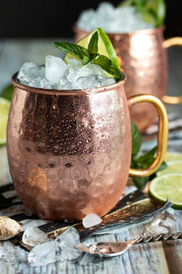 a close up picture of a copper mug with crushed ice, a sprig of mint and a lime