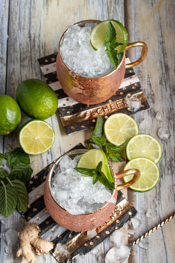 looking down on two moscow mule cocktails in copper mugs with lime wedges