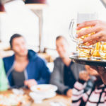 Waiter serving beer at restaurant