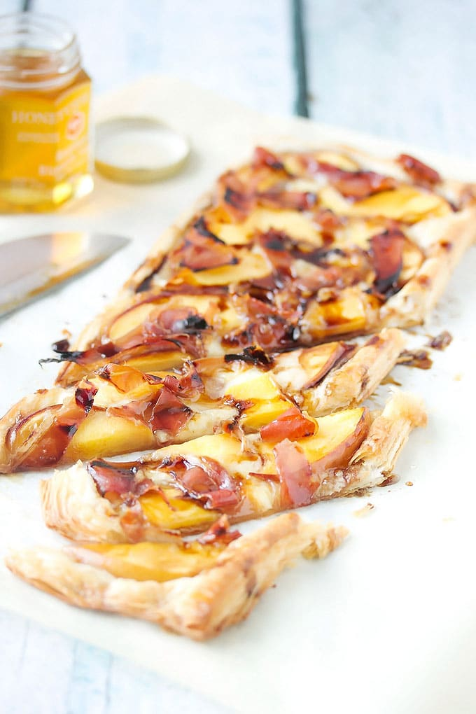 a peach and prosciutto tart that has been cut into a few slices and ready to eat.